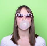 Retrato de la muchacha con los vidrios que hacen el globo con el chicle Imagen de archivo