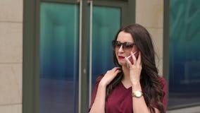 Retrato de la muchacha con un teléfono cerca del edificio moderno almacen de metraje de vídeo