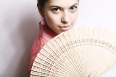 Retrato de la muchacha con un ventilador. Fotografía de archivo