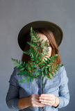 Retrato de la muchacha con una planta en manos imagenes de archivo