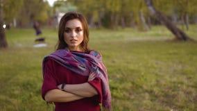 Retrato de la muchacha confiada en manos que cruzan de la bufanda elegante en la cámara en un parque almacen de video