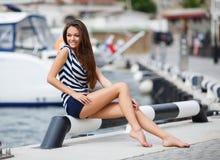 Retrato de la muchacha contra el mar y los yates Foto de archivo libre de regalías
