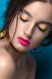 Retrato de la muchacha de la belleza con maquillaje vivo Cierre del retrato de la mujer de la moda para arriba en fondo azul Colo Fotografía de archivo