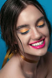 Retrato de la muchacha de la belleza con maquillaje vivo Cierre del retrato de la mujer de la moda para arriba en fondo azul Colo Foto de archivo libre de regalías