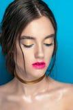 Retrato de la muchacha de la belleza con maquillaje vivo Cierre del retrato de la mujer de la moda para arriba en fondo azul Colo Foto de archivo