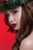 Retrato de la muchacha de la belleza de la Navidad o del Año Nuevo aislado en fondo rojo La mujer hermosa con maquillaje de lujo  fotografía de archivo