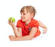 Retrato de la muchacha de la escuela que come la manzana verde aislada Foto de archivo