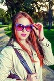 Retrato de la muchacha de moda de Redhair que se coloca en el carril del parque Labios rojos del concepto urbano de la moda y gaf Fotografía de archivo libre de regalías