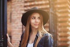 Retrato de la muchacha de moda hermosa que lleva el sombrero negro de ala ancha elegante que mira para arriba Forma de vida de la foto de archivo