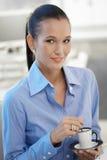 Retrato de la muchacha de oficina que come café Foto de archivo libre de regalías
