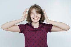 Retrato de la muchacha de risa que guarda su cabeza Imagenes de archivo