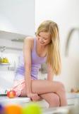 Retrato de la muchacha de risa que se sienta en cocina Foto de archivo