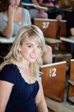Retrato de la muchacha de universidad que se sienta en auditorio Foto de archivo libre de regalías