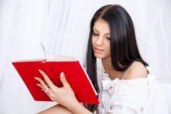 Retrato de la muchacha del adolescente que lee un libro que se sienta en la cama Imágenes de archivo libres de regalías
