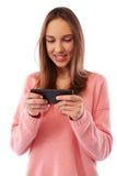 Retrato de la muchacha del adolescente que usa smartphone sobre fondo gris Fotografía de archivo libre de regalías