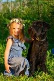 Retrato de la muchacha del beautifull y de su perro negro. Fotografía de archivo libre de regalías
