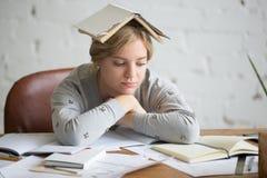 Retrato de la muchacha del estudiante con el libro abierto en su cabeza Fotografía de archivo libre de regalías