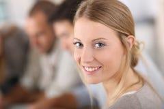 Retrato de la muchacha del estudiante en clase entre otros Foto de archivo