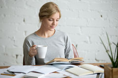 Retrato de la muchacha del estudiante en el escritorio con la taza a disposición Imagen de archivo libre de regalías