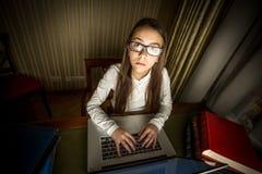Retrato de la muchacha del friki del ordenador que se sienta en el ordenador portátil en la noche Fotos de archivo