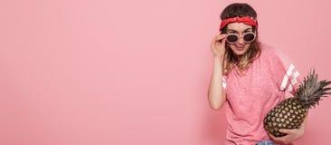 Retrato de la muchacha del inconformista en vidrios y piña en fondo rosado imagen de archivo libre de regalías