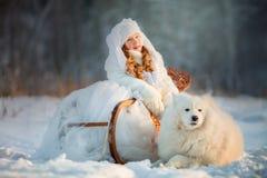 Retrato de la muchacha del invierno con el perro del samoyedo imagenes de archivo