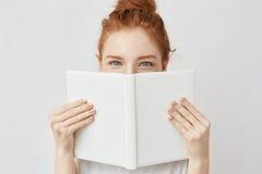 Retrato de la muchacha del jengibre que oculta detrás del libro que mira la cámara Foto de archivo