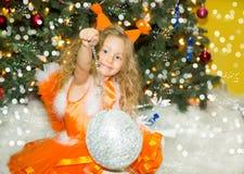 Retrato de la muchacha del niño en ardillas de un traje alrededor de un árbol de navidad adornado Niño en Año Nuevo del día de fi Foto de archivo