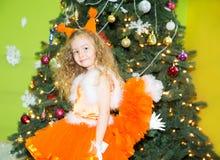 Retrato de la muchacha del niño en ardillas de un traje alrededor de un árbol de navidad adornado Niño en Año Nuevo del día de fi Imagen de archivo libre de regalías