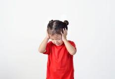 Retrato de la muchacha del preescolar que tiene un dolor de cabeza imagen de archivo