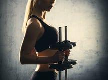 Retrato de la muchacha delgada, sana y deportiva con pesas de gimnasia Mujer rubia que presenta en ropa de deportes Fotografía de archivo libre de regalías