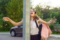 Retrato de la muchacha desatenta joven, distraído por el teléfono móvil La muchacha se estrelló en los posts de la calle, teléfon imagen de archivo libre de regalías