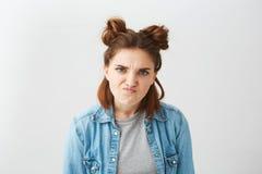 Retrato de la muchacha descontentada enojada de la rabia con los bollos que miran la cámara brutal sobre el fondo blanco Fotos de archivo