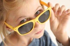 Retrato de la muchacha divertida del adolescente en gafas de sol en el fondo blanco Imágenes de archivo libres de regalías