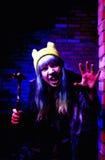 Retrato de la muchacha divertida del zombi en el tiempo de Halloween con el martillo Foto de archivo
