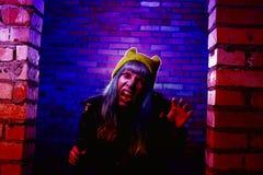 Retrato de la muchacha divertida del zombi en el tiempo de Halloween con el martillo Imagen de archivo libre de regalías