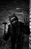 Retrato de la muchacha divertida del zombi en el tiempo de Halloween con el martillo Fotos de archivo