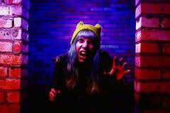 Retrato de la muchacha divertida del zombi en el tiempo de Halloween con el martillo Imágenes de archivo libres de regalías