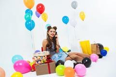 Retrato de la muchacha divertida que toma la conversación telefónica que se sienta en piso Imagen de archivo