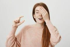 Retrato de la muchacha emotiva divertida del jengibre que cubre un ojo mientras que muestra algo pequeño o minúsculo con gesto y  Fotografía de archivo