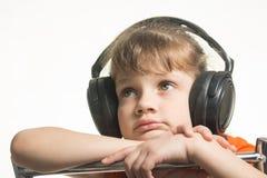 Retrato de la muchacha en auriculares que escucha la música musical Imagen de archivo
