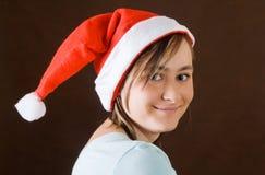 Retrato de la muchacha en el sombrero de Papá Noel Imagen de archivo