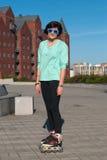Retrato de la muchacha en gafas de sol divertidas, que rollerblading en el A.C. Foto de archivo