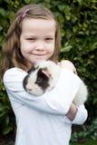 Retrato de la muchacha en jardín que se ocupa el conejillo de Indias del animal doméstico Imagen de archivo libre de regalías