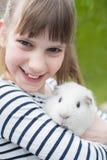 Retrato de la muchacha en jardín que se ocupa el conejillo de Indias del animal doméstico Foto de archivo libre de regalías