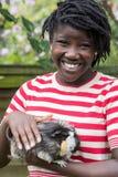 Retrato de la muchacha en jardín que se ocupa el conejillo de Indias del animal doméstico Imagenes de archivo