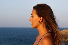 Retrato de la muchacha en la playa durante puesta del sol Fotos de archivo libres de regalías