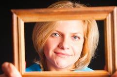 Retrato de la muchacha en un marco de madera Imagenes de archivo