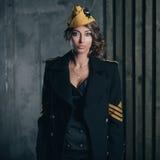 Retrato de la muchacha en un uniforme negro del aviador con el sombrero Imagen de archivo