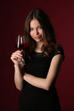 Retrato de la muchacha en vestido negro con el vino Cierre para arriba Fondo rojo oscuro Imagenes de archivo